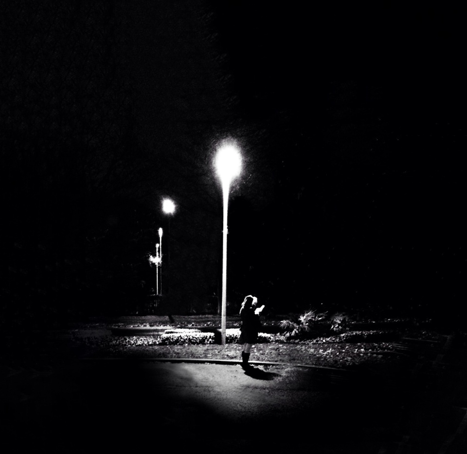 Girl Reading Under A Lamp Post In The Rain